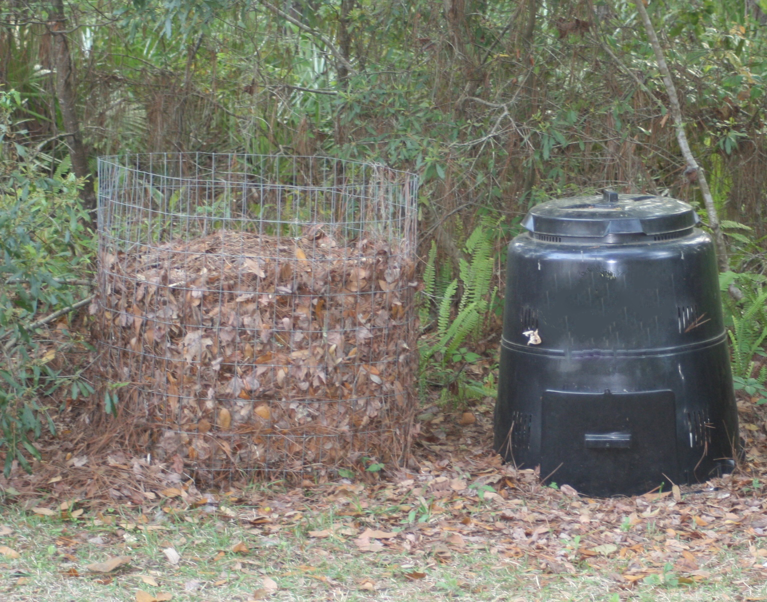 Two different types of backyard composters. One is a wire bin, the other is plastic.
