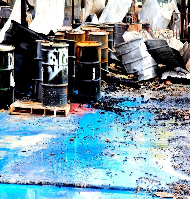 Oil drums with spilled oil on the ground